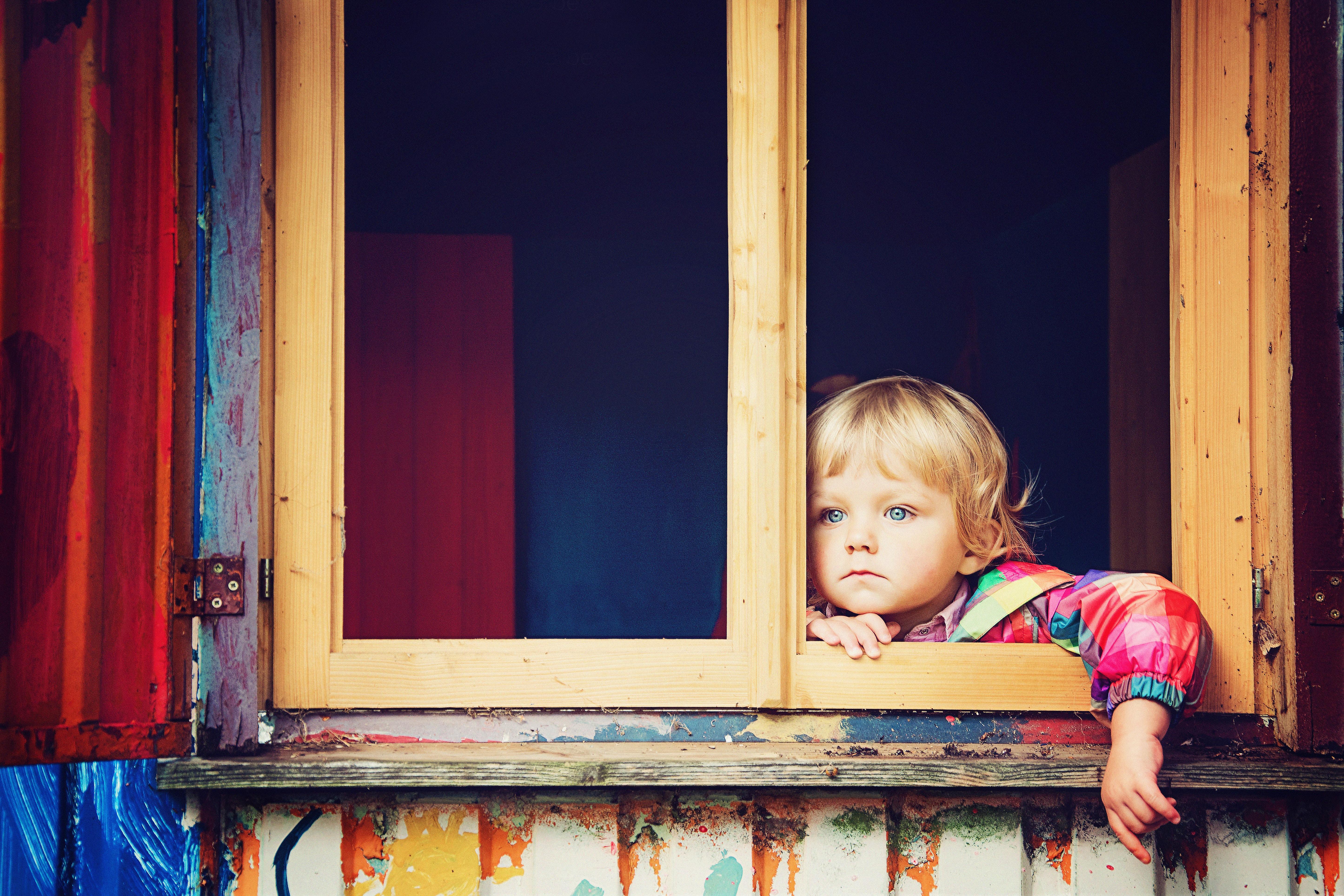 窓から外をみる少年
