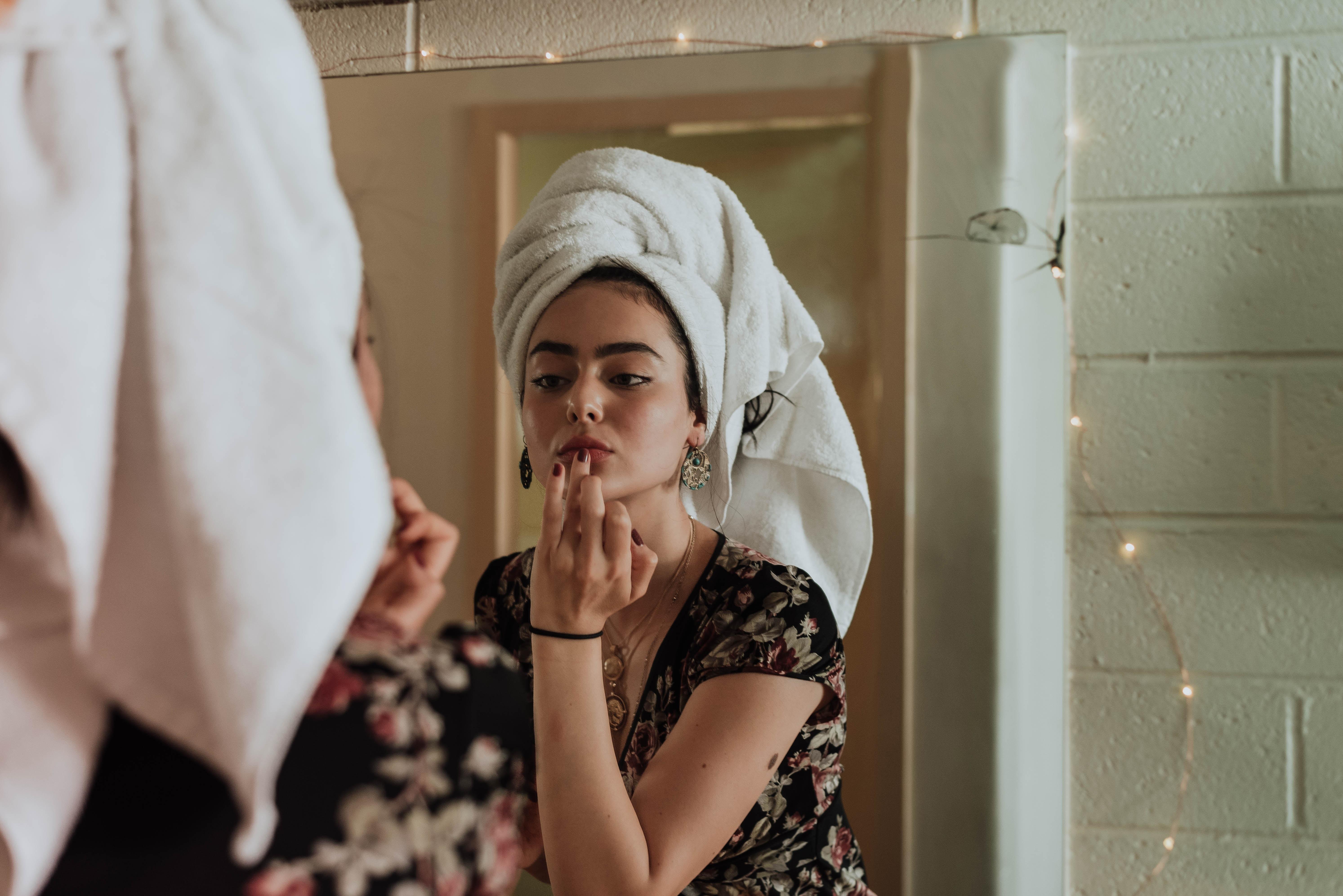 鏡をみて化粧をする女性