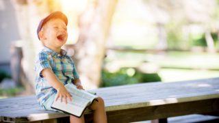 本を開いて笑う男の子