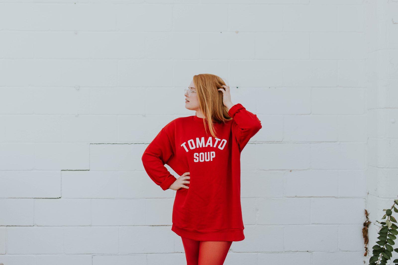 白い壁に赤いワンピースの女性