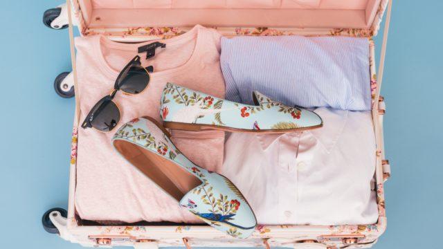 花柄のスーツケースにサングラスとパンプス